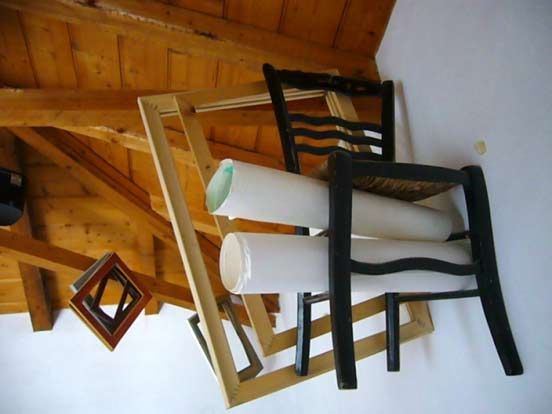 a creative approach to storage: frames, canvasses and a chair hung from the roof beams!